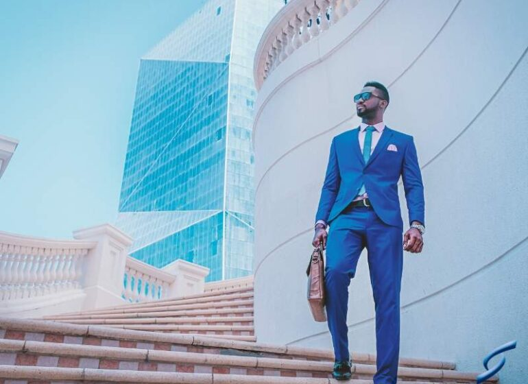 Successful, creative businessman on steps of office building